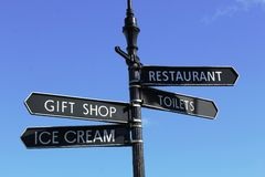 Signpost showing Gift Shop, Ice cream, Toilets, Restaurant. A black metal theme park sign showing the way to the Restaurant, Gift Shop, Toilets and Ice cream Royalty Free Stock Photos