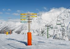 Signpost in the ski resort of La Thuile, pointing towards different pistes including to the French resort of La Rosiere. La Thuile, Italy - Feb 18, 2018 Royalty Free Stock Photo