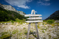 Signpost with three directions on the foot of big mountain Stock Photos