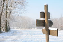 Signpost in Wintry countryside. Blank wooden signpost in Wintry countryside with trees in background stock photos