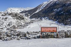 Signpost written in various languages warning of expert ski run ahead. View of Thuile town in valley below Valle d`Aosta, Italy royalty free stock images