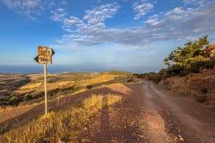 Signposted грязная улица с взглядом над морем на острове Кипра Стоковое Изображение RF