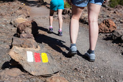 Signposted with Spanish flags colors hiking route to Lunar landscape Paisaje Lunar. Woman and child legs passing stone trail, Te Stock Photo
