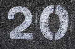 Signposting. Number twenty painted white on asphalt stock photo