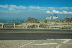 Signposts with town directions on road crossing rocky landscape. And bush fields, at the highlands of the Serra da Estrela. The highest mountain range in royalty free stock photography