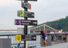 Signposts on the waterfront on Podil, Ukraine, Kyiv. Landscape with a view of Pedestrian bridge over the Dnipro river at sunset Royalty Free Stock Image