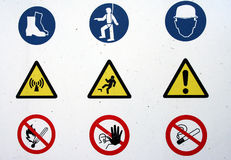 Signs. Picture of a white board with  signs : a.o. no smoking, danger, no fire, wear a helmet, etc Stock Images