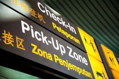 Signs at the airport Check-in and Pick-Up Zone Stock Image