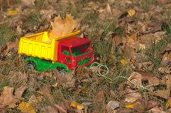 Signs of autumn - a forgotten toy in the park. Among grass and leaves Stock Photography