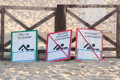 Signs - bathing place, storm, swimming prohibited and swimming forbidden - lie on the sandy be Stock Photos