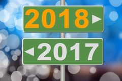 Signs 2017 and 2018 on a blurred background. Collage Royalty Free Stock Image