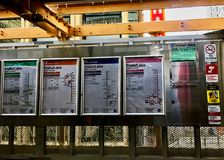 Signs for the different colored CTA train lines hang in station at State & Lake Streets in downtown Chicago Loop Stock Photos