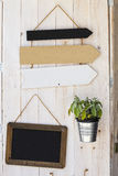 Signs empty arrow. Retro arrows. Decoration wooden background. Signs for the pointing. Some signs with arrows. A blackboard. A pot with small plant. Signs royalty free stock images