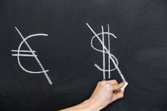 Signs of euro and dollar crossed on blackboard by hand Stock Photos