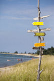 Signs Everywhere. A wooden sign post pointing in all directions on a lake beach in the summer Stock Images
