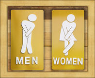 Signs female and male bathroom on wooden background. Royalty Free Stock Images