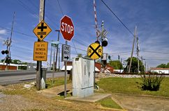 Signs in front of a railroad crossing. A series of road signs on a busy street are in front of a city railroad crossing Stock Images