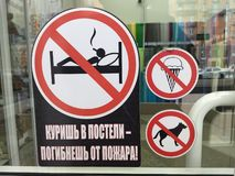 "Signs ""no ice cream"", ""no dogs"" and ""no smoking in bed"" on the door of a shop royalty free stock image"