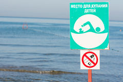 Signs a -place for bathing children and non-smoking - on sea background Royalty Free Stock Photography