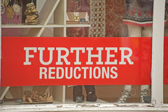 Signs of recession; further price reductions. An image of a sign ' further reductions '  in a shop window showing that retail sales require continuing stimulus Stock Photo