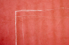 Signs on a red wall. Chalk lines drawn by children to delineate the pole of a football goal Royalty Free Stock Images