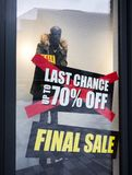 Signs of sale in shop windows of clothing store. Big letters indicate sale in shop windows of clothing store Stock Photos