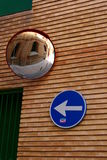 Signs on street in Zaragoza. Directional arrow on the blue rounded sign and a brick wall with a mirror royalty free stock images