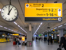 Signs terminal Schiphol Amsterdam Airport, Holland. Signs, clock and travellers in terminal of Schiphol Amsterdam Airport, Netherlands Royalty Free Stock Images