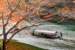 Signtseeing Arashiyama at autumn, Kyoto. ARASHIYAMA, JAPAN - NOVEMBER 23, 2017: Unidentified people on tourist boat to signtseeing Arashiyama with autumn foliage Royalty Free Stock Photo