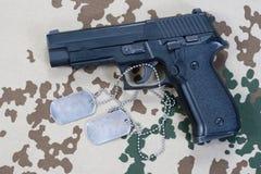 Sigsauer-Faustfeuerwaffe und -Erkennungsmarken Stockfoto