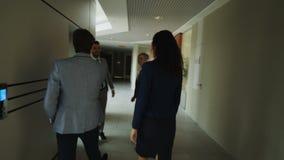 Siguiendo el tiro de la empresaria y del hombre de negocios que hablan que caminan en el pasillo y que encuentran a colegas y ven almacen de metraje de vídeo