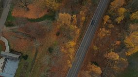 Sigulda city autumn road car drive from above. Drone flight with drone above autumn road with car stock footage