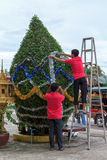 SIHANOUKVILLE, CAMBODIA - DECEMBER 05. 2014 Unidentified asian male workers decorate a new year tree in the street on December 05, 2014 in Sihanoukville Royalty Free Stock Photography