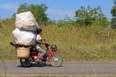 SIHANOUKVILLE, CAMBODIA - NOVEMBER 18, 2014. Unidentified man drives overloaded motorcycle in Sihanoukville, Cambodia royalty free stock photos