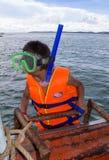 SIHANOUKVILLE, CAMBOJA - POSSA 18, 2014: Um rapaz pequeno em uma máscara para mergulhar vai para baixo no mar perto de Sihanokvil Imagens de Stock