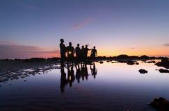 Sihleoutte d'un groupe des hommes pendant le coucher du soleil Photographie stock libre de droits