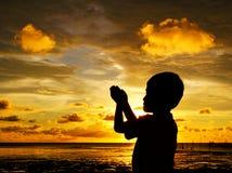 Sihlouette da criança rezando durante o por do sol Fotos de Stock