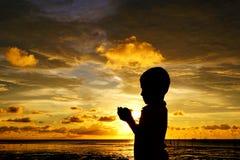 Sihlouette modlenie dzieciak podczas zmierzchu Obrazy Royalty Free