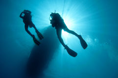 Sihlouetted scuba divers. Shilouetted scuba divers swim in the deep blue ocean Stock Images