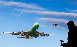 Sihouette человека летая трутень около причаливая воздушного судна стоковые фотографии rf