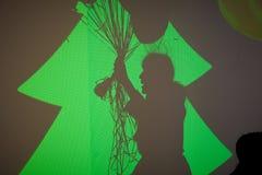 Sihouette de la mujer con los globos en la pared verde Fotos de archivo