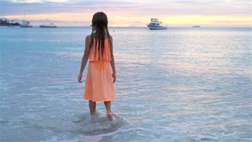 Sihouette of little girl on the beach at sunset. Sihouette of little girl walking on the beach at sunset stock video