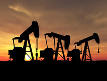 Sihouette three oil pumps. Three pumps over orange sky Royalty Free Stock Image
