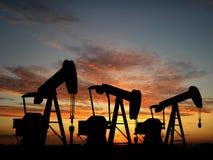 Sihouette tres bombas de petróleo Fotos de archivo libres de regalías