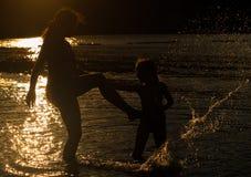 Sihouetted母亲和女儿在海边 免版税库存图片