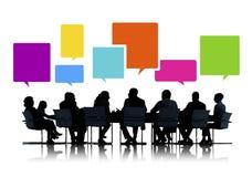 Sihouettes de hombres de negocios en una reunión con las burbujas del discurso Imagen de archivo libre de regalías