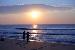 Sihoulettes surf fishing at sunrise. Two people surf fishing at the sea shore on a beautiful Summer morning in New Jersey. USA Stock Images