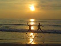 A sihouted jongen en meisjessprong met geluk op het zandige strand als zonreeksen stock afbeelding