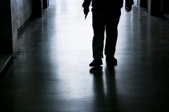 Siilhouette de un hombre que lleva a cabo el objeto agudo disponible mientras que acercamiento Foto de archivo