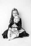 Siisters. Two sisters: 6 years old and 6 months old wearing beautiful dresses and head decorations, sitting against white fluffy background. Styled as high stock photography